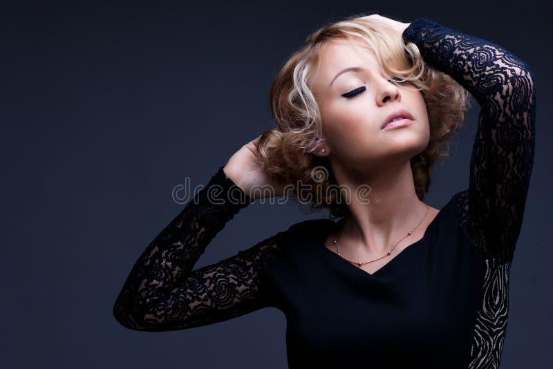 Schöne blonde Frau mit elegantem schwarzem Kleid lizenzfreie stockbilder