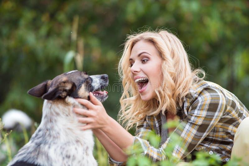 Schöne blonde Frau mit Hund im grünen Garten lizenzfreies stockfoto