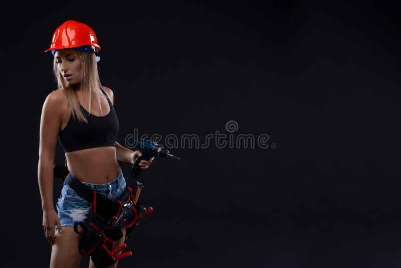 Schöne blonde Frau mit schwerem Perforator in ihren Händen lizenzfreie stockbilder