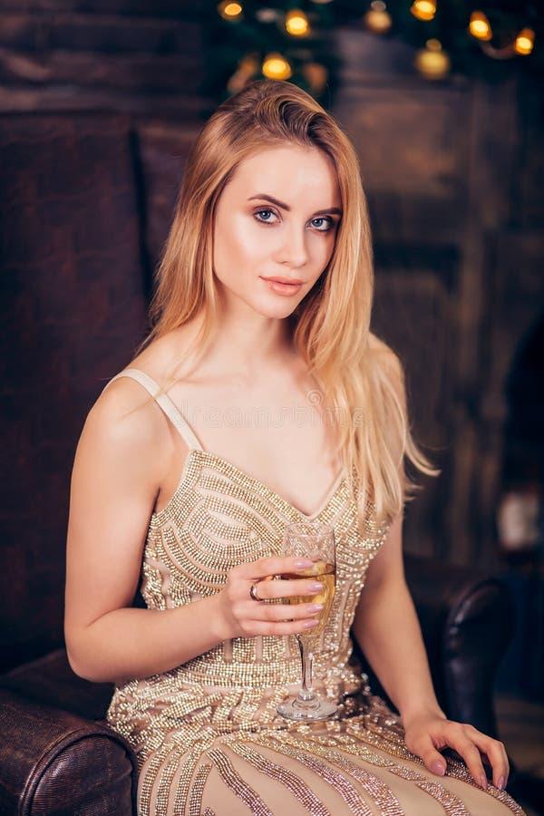 Schöne, blonde Frau trägt ein Goldabendkleid, hält an Hand ein Glas Champagner und somtret zum cmaera auf dem Weihnachten stockfoto