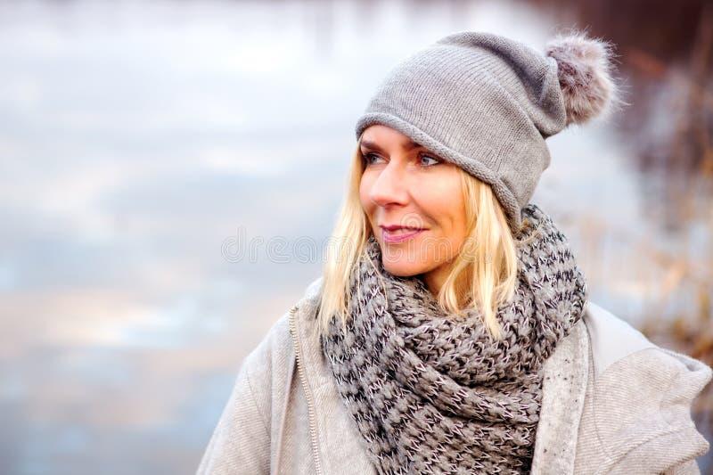 Schöne blonde Frau vor See stockbilder