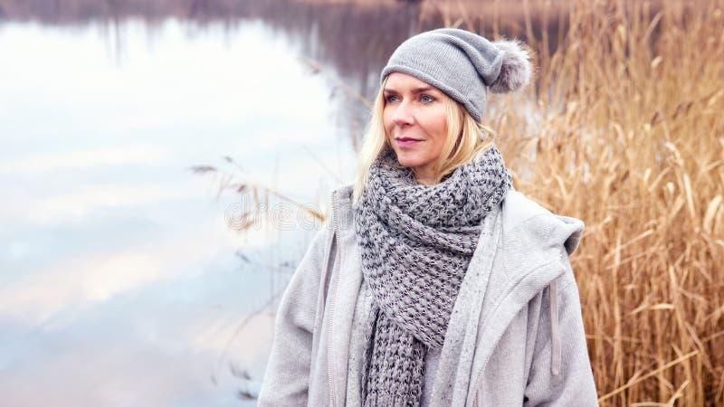 Schöne blonde Frau vor See lizenzfreie stockfotografie