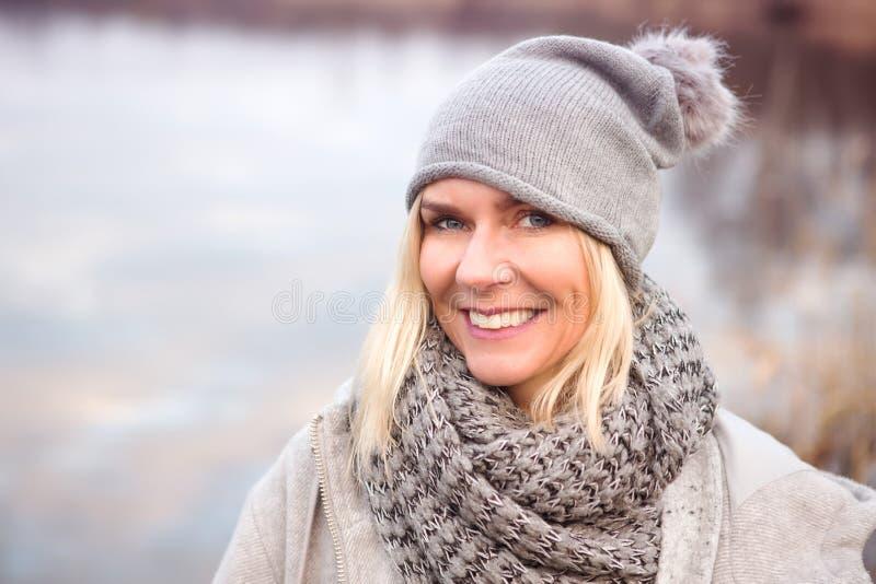 Schöne blonde Frau vor See lizenzfreies stockbild