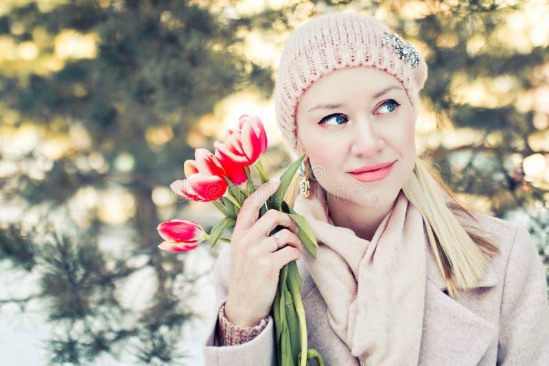 Schöne blonde Frau in Winter biege Kleidung mit Blumen Portrate im Freien mit Unschärfe lizenzfreies stockbild