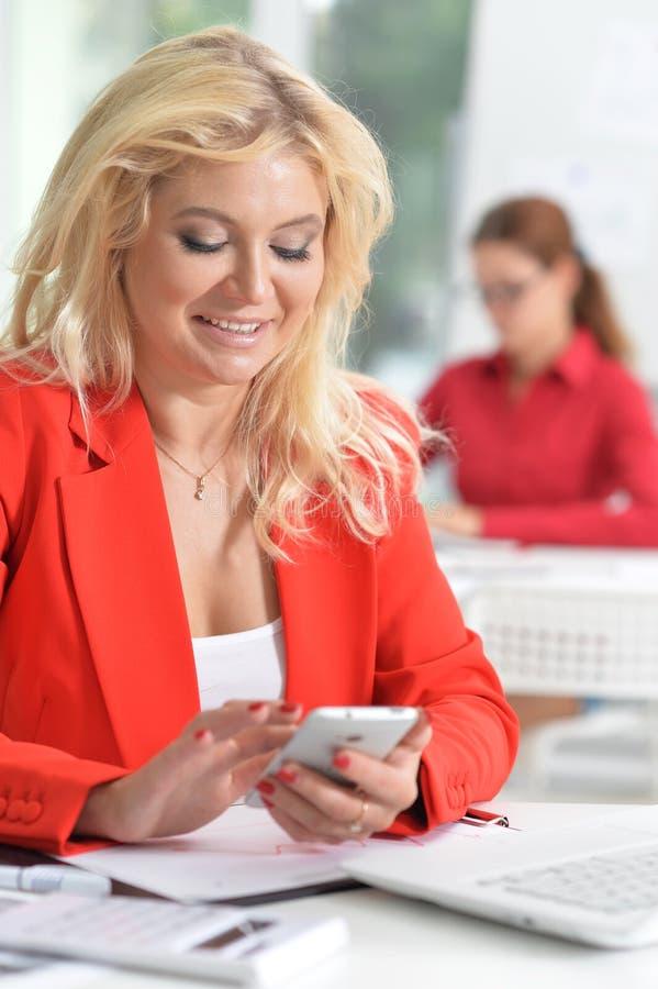 Schöne blonde Geschäftsfrau in der roten Jackenfunktion lizenzfreie stockfotos