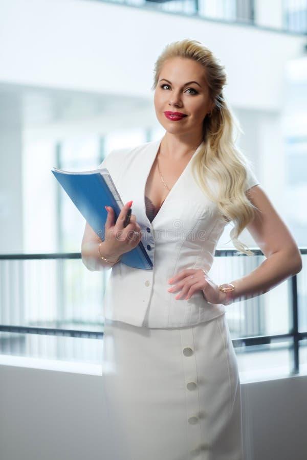 Schöne blonde Geschäftsfrau mit Dokumenten stockbild