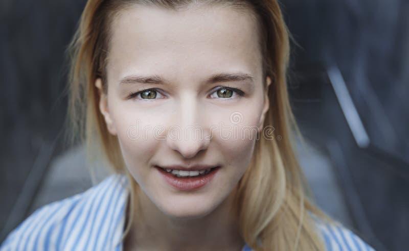 Schöne blonde Jugendliche, die in Kamera lächelt tag lizenzfreies stockfoto