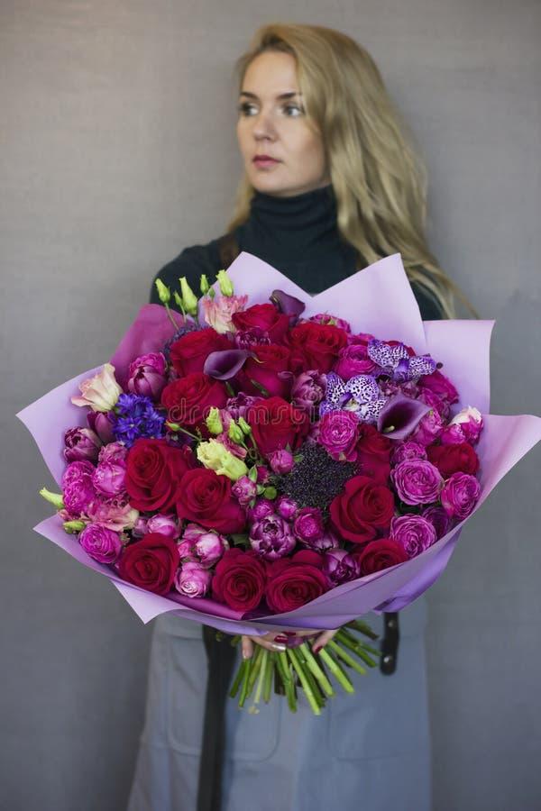 Schöne blonde junge Frau, die im Handgroßen Blumenstrauß hält lizenzfreies stockfoto