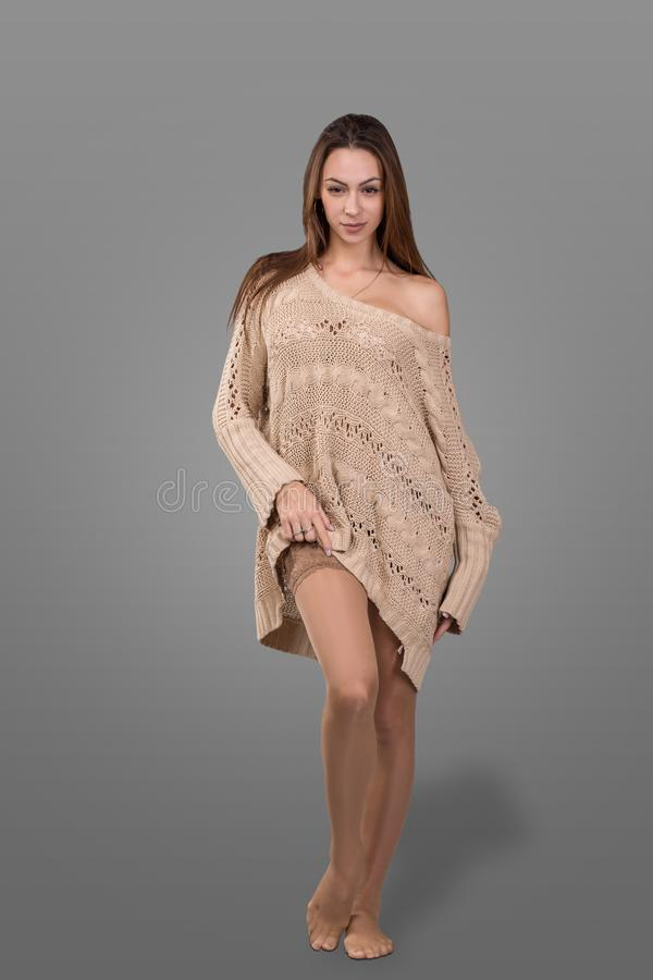 Schöne blonde junge Frau in gestricktem Pullover und in Strümpfen steht auf grauem Hintergrund lizenzfreie stockfotografie