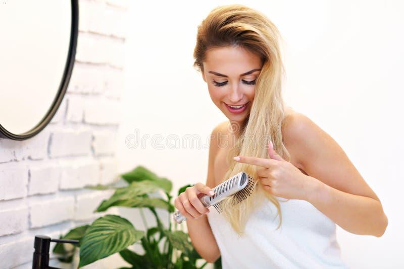 Schöne blonde kaukasische Frau, die im Badezimmer mit dem nass Haar aufwirft stockfotografie