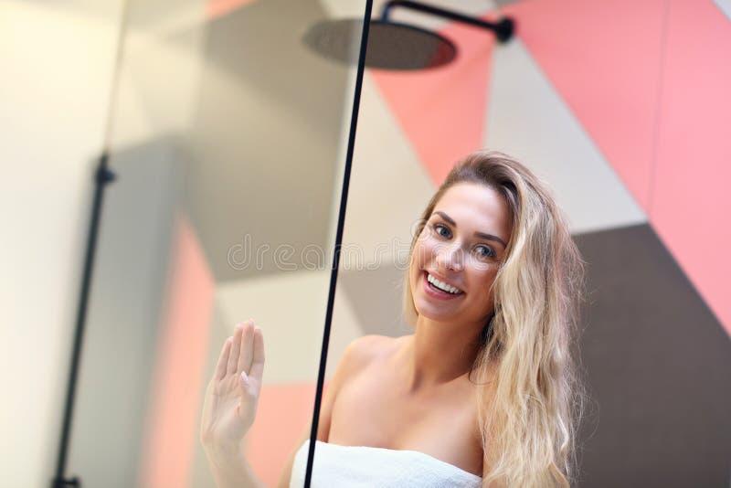 Schöne blonde kaukasische Frau, die im Badezimmer mit dem nass Haar aufwirft lizenzfreie stockbilder