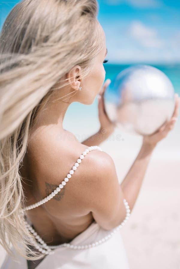 Schöne blonde lange Haarbraut im langen weißen Kleid auf dem Strand mit Perle Tropisches turquois Meer auf dem Hintergrund lizenzfreies stockbild