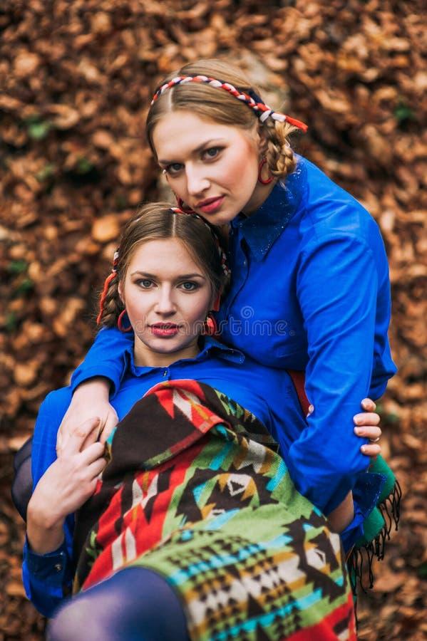 schöne blonde Schwestern paart im Herbstwald stockfotografie