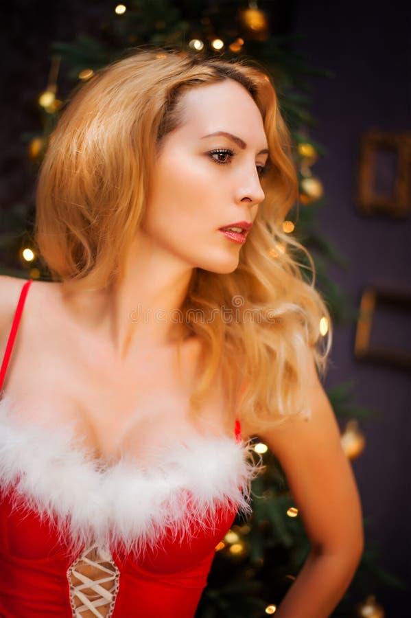 Schöne blonde sexy Frau im roten Weihnachtskleid lizenzfreies stockbild