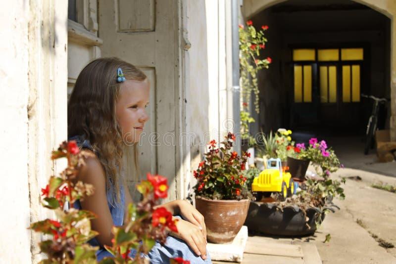 Schöne blonde tragende Jeans des kleinen Mädchens kleiden an und sitzen auf einem Portal in einem alten Garten stockbilder