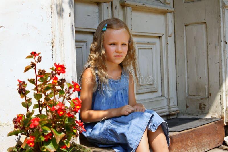 Schöne blonde tragende Jeans des kleinen Mädchens kleiden an und sitzen auf einem Portal in einem alten Garten lizenzfreie stockbilder