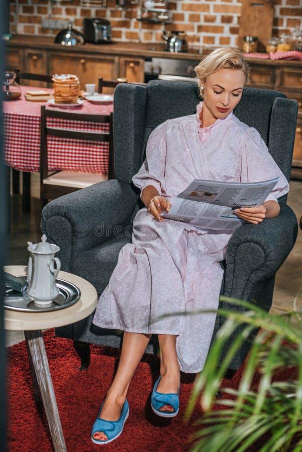 schöne Blondine in der Robenlesezeitung zu Hause lizenzfreies stockbild