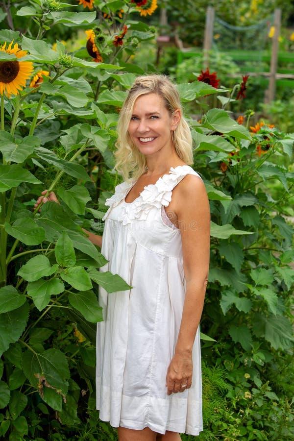 Schöne Blondine in der weißen Kleiderstellung im Garten stockfoto