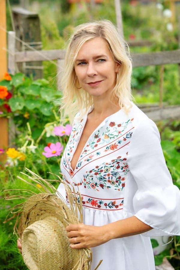 Schöne Blondine in der weißen Kleiderstellung im Garten stockfotos