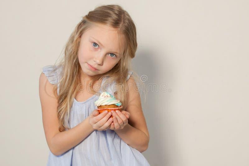Schöne Blondine des kleinen Mädchens mit Kuchen- und Süßigkeitsporträt der Nahrung stockfotografie