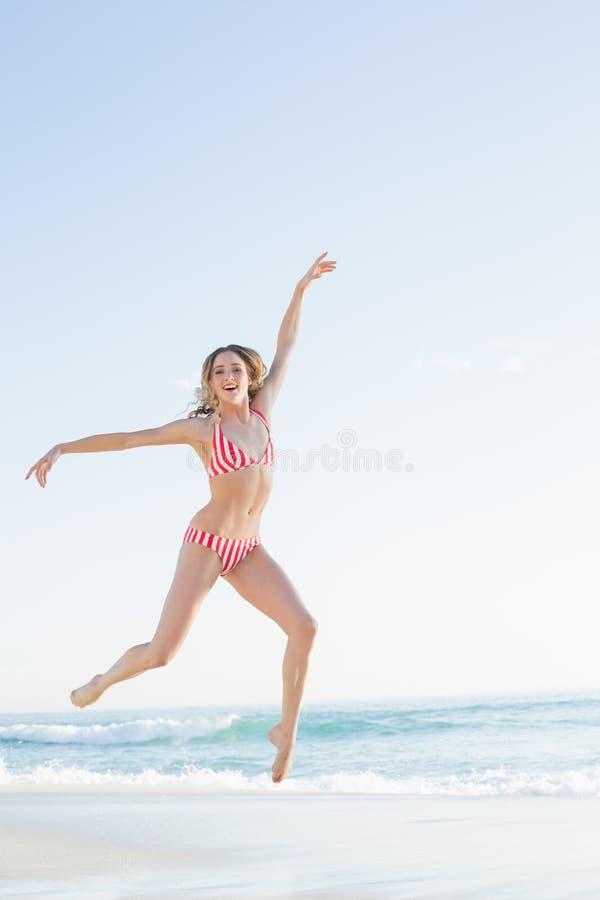 Schöne Blondine, die auf den Strand springen stockfotos