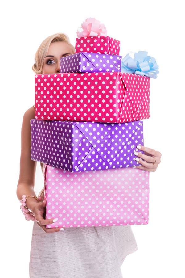 Schöne Blondine, die durch bunte Geschenkboxen schauen lizenzfreie stockbilder