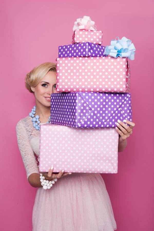 Schöne Blondine, die durch bunte Geschenkboxen schauen Weiche Farben Weihnachten, Geburtstag, Valentinstag, vorhanden stockfoto