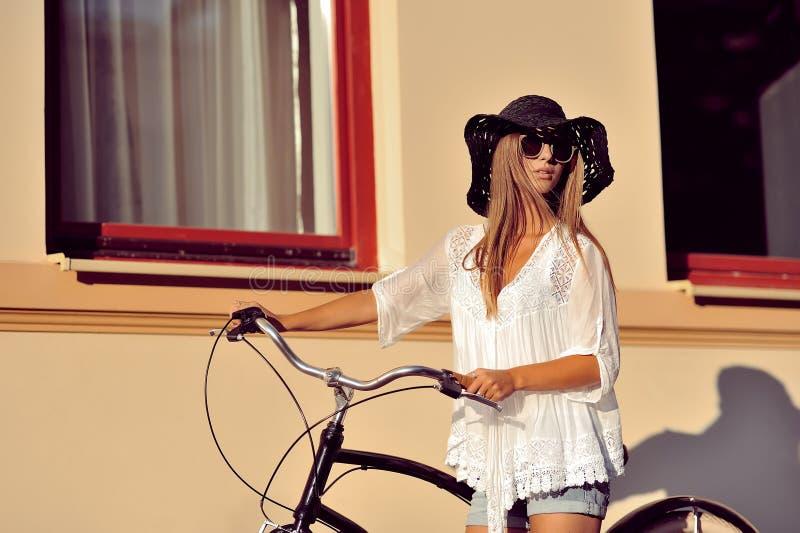 Schöne Blondine, die nahe ihrem alten Fahrrad steht Im Freienart und weise stockfotos
