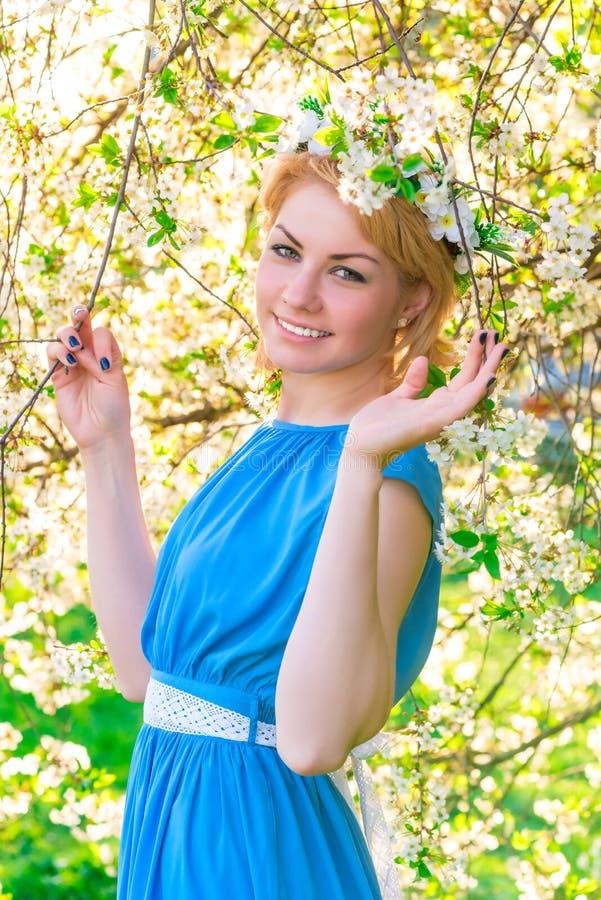Schöne Blondine in einem blauen Kleid stockfotografie