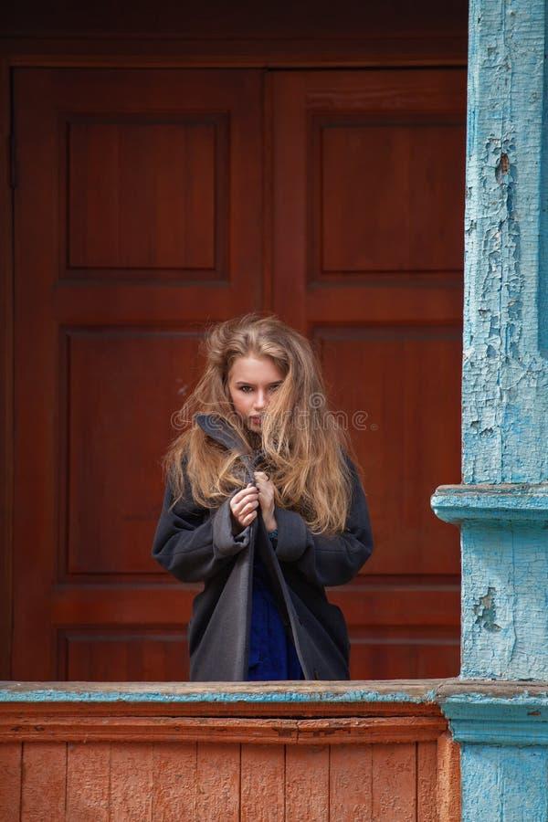 Schöne Blondine in einem hellgrauen Mantel lizenzfreies stockfoto
