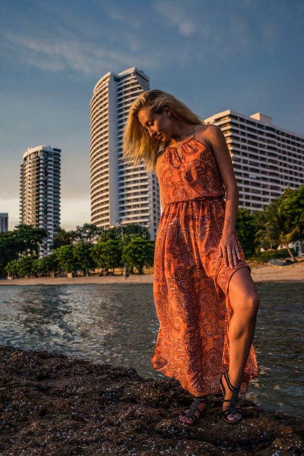 Schöne Blondine in einem hellroten Kleid steht das Meer auf dem luxuriösen Erholungsort des Hintergrundes Ende des Nachmittagsson lizenzfreies stockfoto