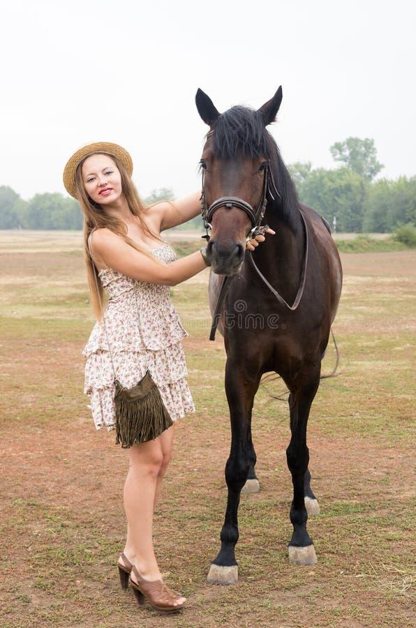 Schöne Blondine in einem Strohhut und Sommer kleiden an, fotografiert mit einem Pferd lizenzfreie stockfotos