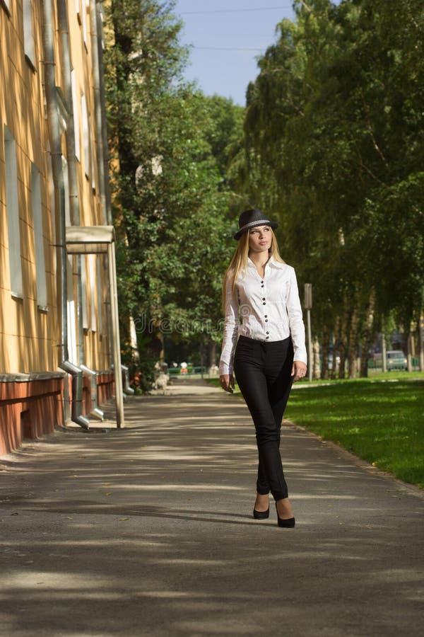 Schöne Blondine in einer weißen Bluse und in einem Hut lizenzfreies stockfoto