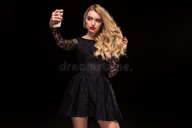 Schöne Blondine im schwarzen Kleid und bilden das Nehmen von selfie mit dem Handy, der auf dem schwarzen Hintergrund lokalisiert  stockfotos