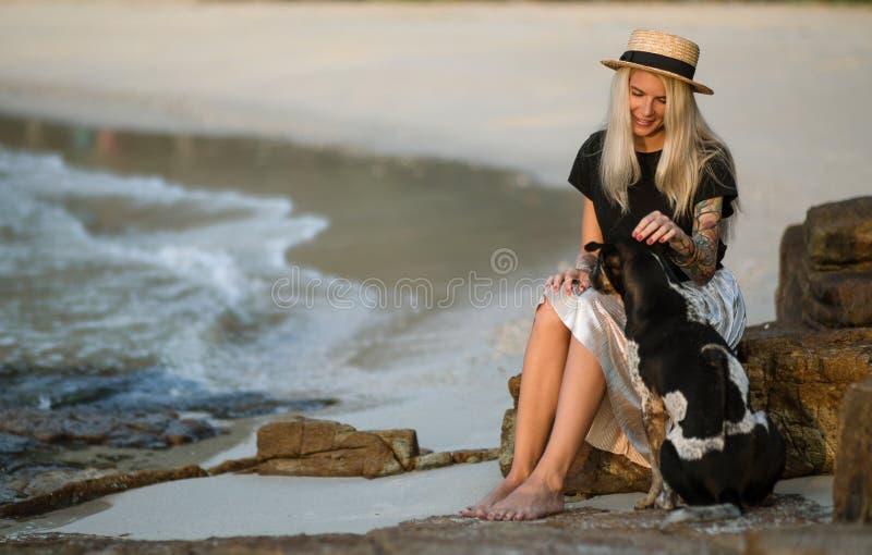 Schöne Blondine im Strohhut, der auf einem Felsen sitzt und den guten Hund streichelt Die gleiche Farbe Siamesischer Strand Morge lizenzfreies stockfoto