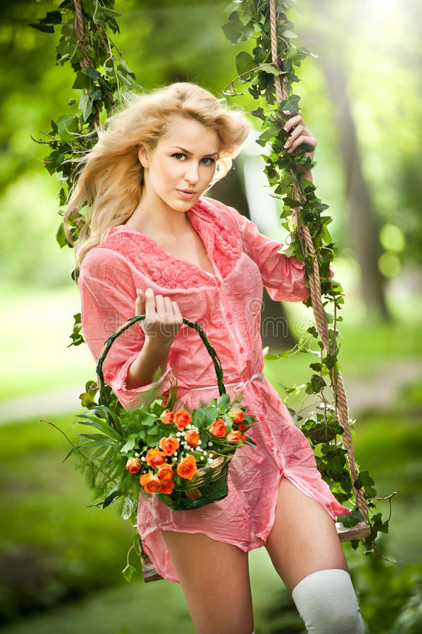 Schöne Blondine mit Blumenkorb im belaubten Schwingen lizenzfreie stockfotos