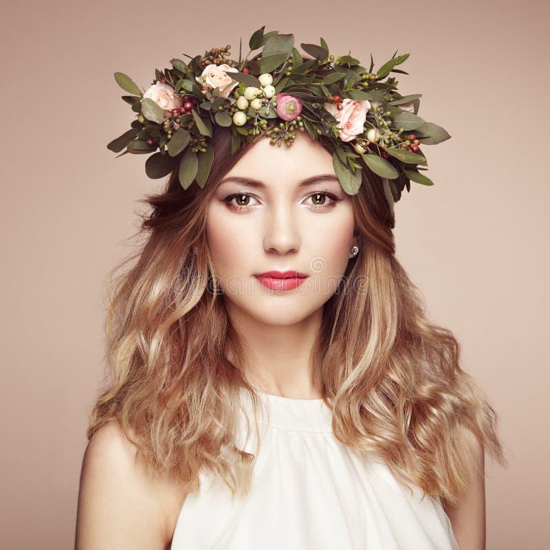 Schöne Blondine mit Blumenkranz auf ihrem Kopf lizenzfreie stockfotos