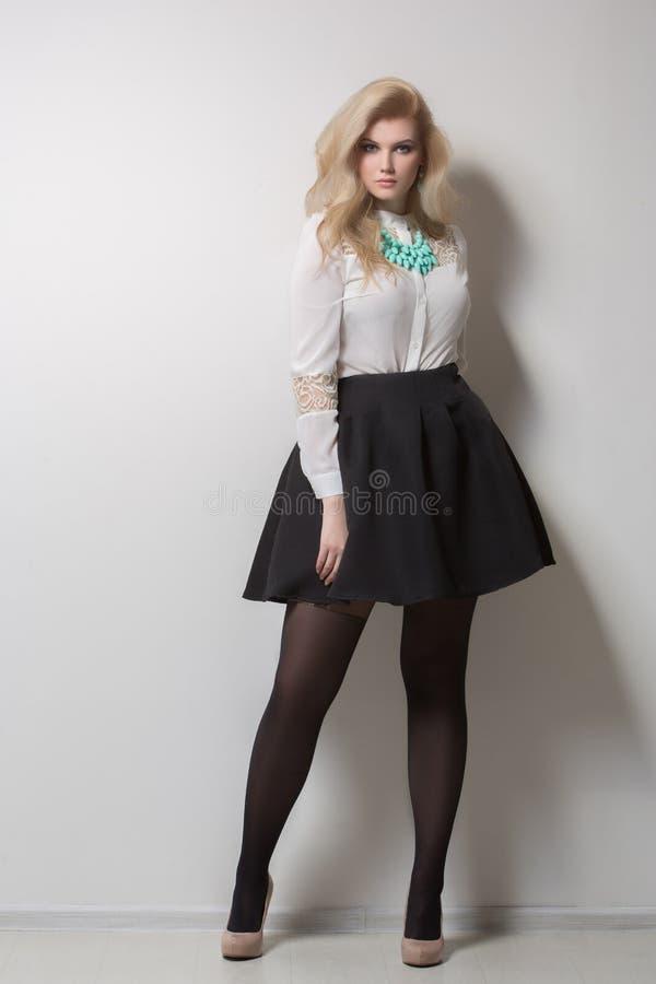 Schöne Blondine mit dem langen Haar in einem Rock dick lizenzfreies stockfoto