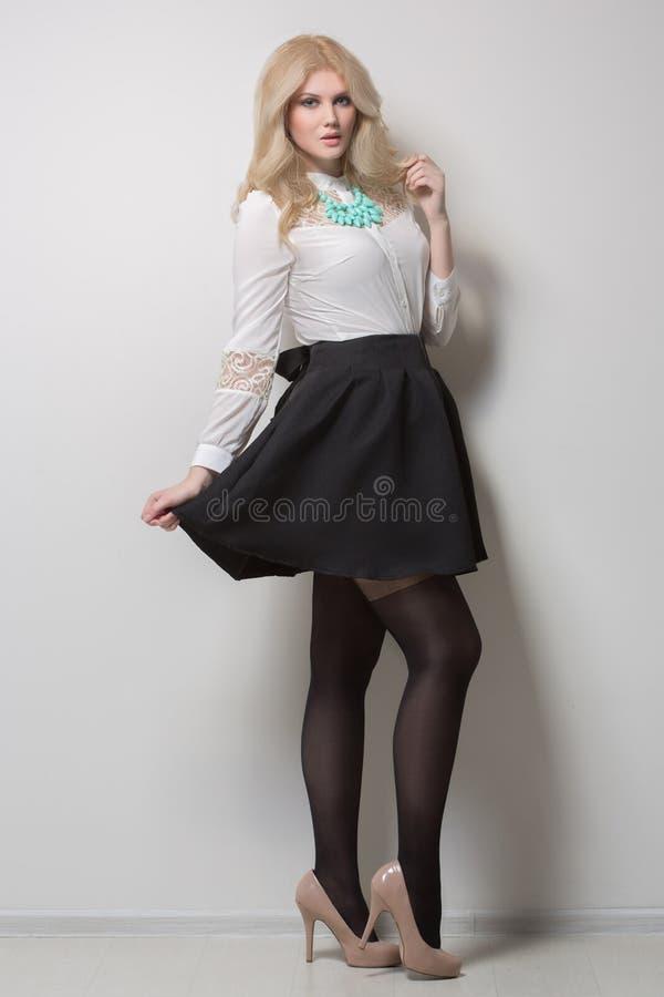 Schöne Blondine mit dem langen Haar in einem Rock dick stockfotografie