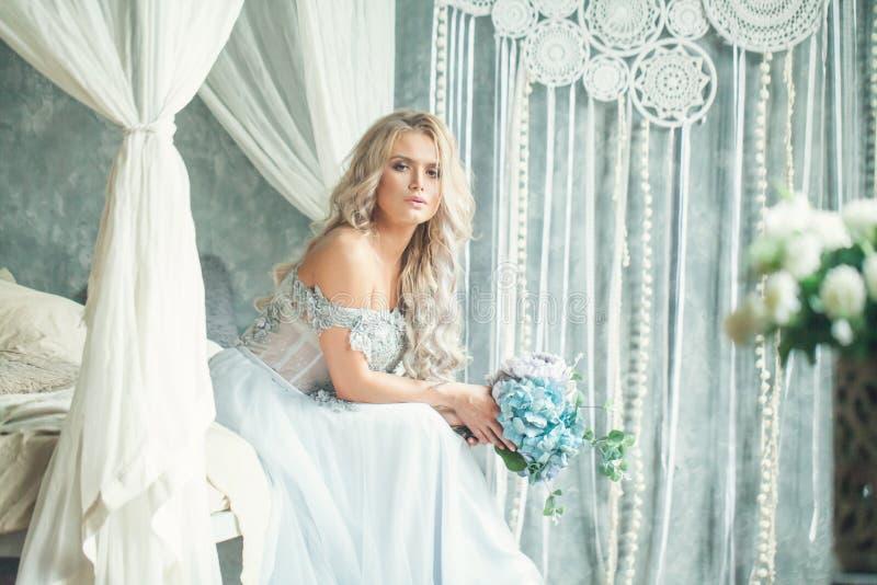 Schöne Blondine mit den Blumen, die im Weinleseinnenraum sich entspannen stockfotografie