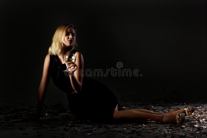 Schöne Blondine mit Glas Weißwein auf schwarzem Hintergrund lizenzfreie stockfotografie