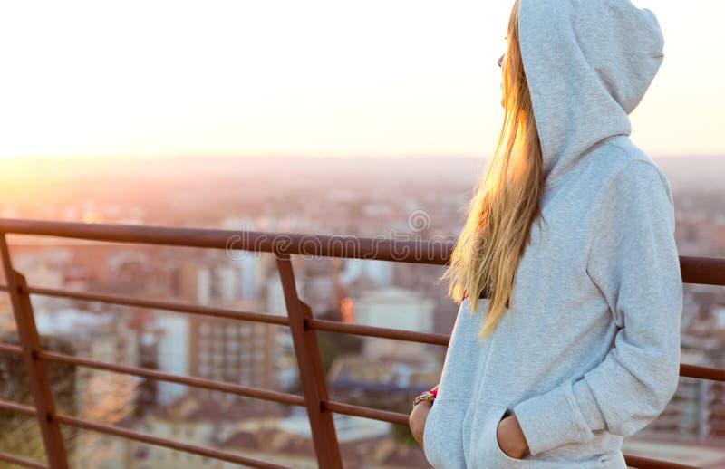 Schöne Blondine steht am Rand des Dachs lizenzfreie stockfotos
