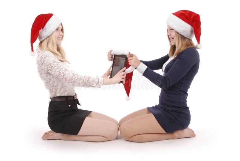 Schöne Blondine zwei in Weihnachtsmann-Hut mit Tabletten-PC lizenzfreie stockfotografie