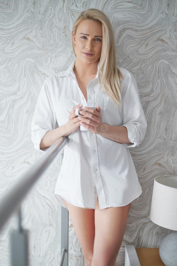 Schöne Blondinestellung nahe bei einem Fenster in einer Dachbodenwohnung stockbild