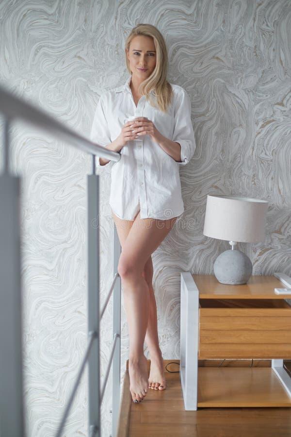 Schöne Blondinestellung nahe bei einem Fenster in einer Dachbodenwohnung lizenzfreies stockbild
