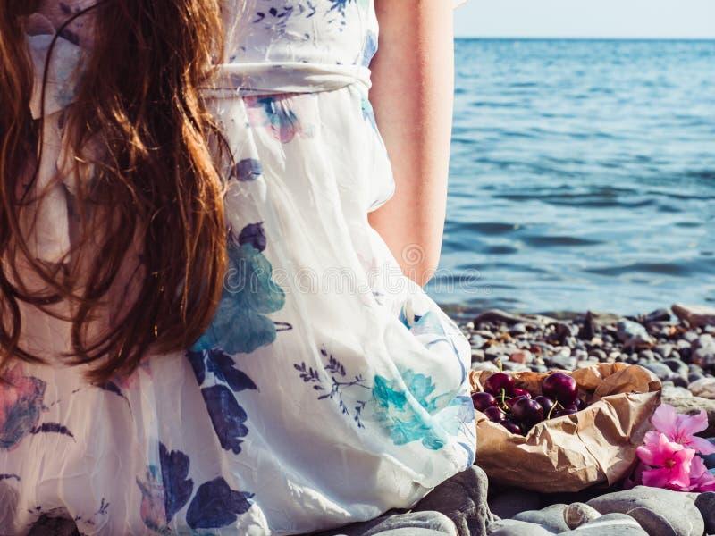 Schöne Blume und ein einsames Mädchen mit dem langen Haar stockfoto