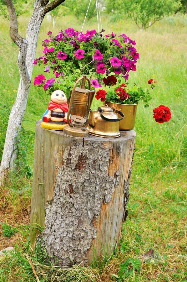Schöne Blumen in einem Topf auf einem Stumpf lizenzfreies stockbild
