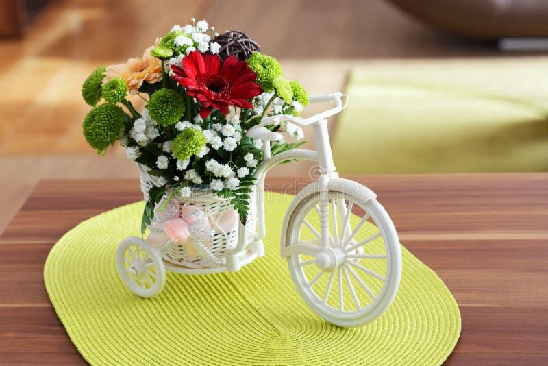 Schöne Blumen in einem weißen Fahrrad auf Holztisch lizenzfreies stockfoto