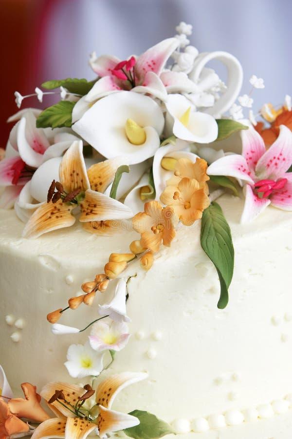 Schöne Blumen oben auf einen Hochzeitskuchen lizenzfreie stockfotos