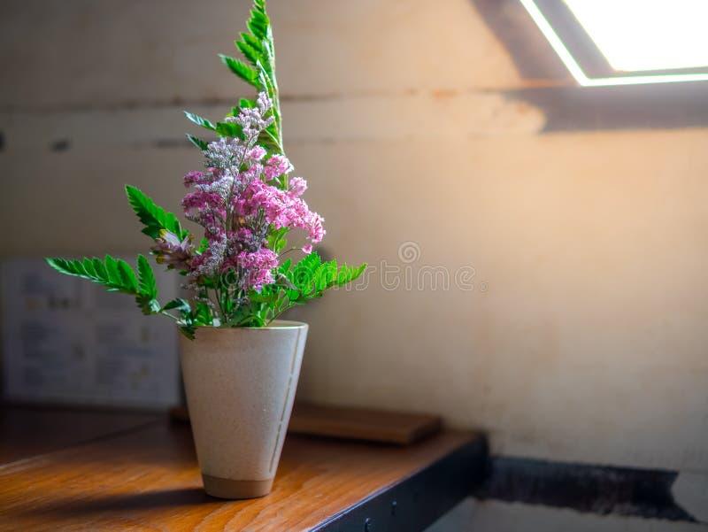 Schöne Blumen rosa und grüne Blätter in einer weißen Vasenweinlese auf dem Holztisch neben Fensterbeleuchtung stockbild